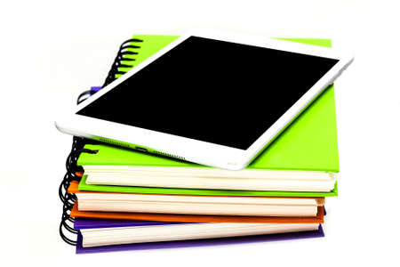 stack of ring binder book or notebook with tablet computer isolated on white photo