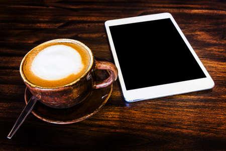 デジタル タブレットと木製のテーブルでコーヒー カップ 写真素材