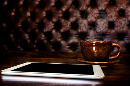 digital tablet and coffee cup on wooden table Stock Photo - 21061183