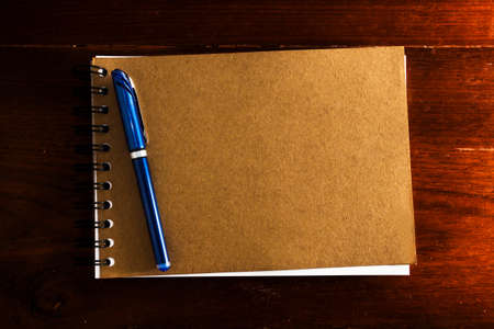 Old vintage note book with pen on wooden table