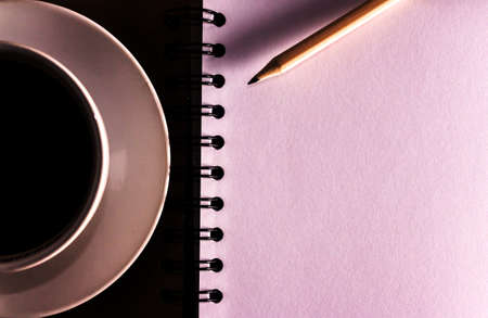 Open a blank white notebook, pencil and cup of coffee on the desk photo