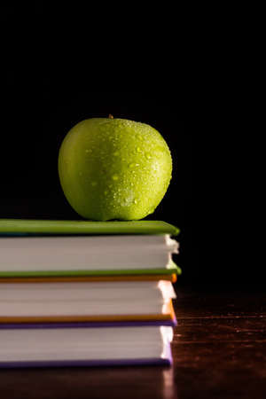 Stack books and green apple photo