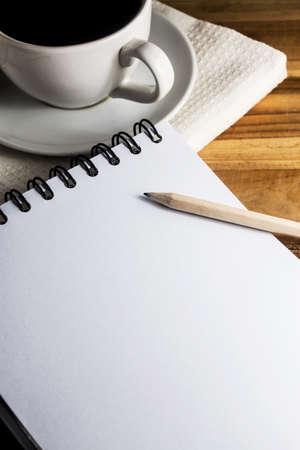 紙と鉛筆とコーヒーの白いカップ付きの仕事机
