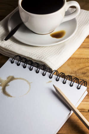 coffee stain: paper, pencil and white cup of coffee on desk