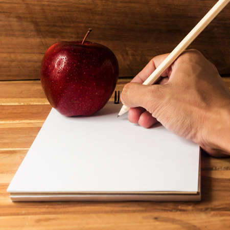 Hand writing and Fresh apple with drops of water on deask