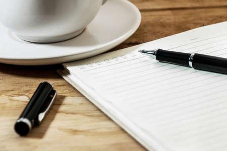 まで開いている閉じて空白の白いノートブック、ペン、机の上のコーヒーを 1 杯 写真素材