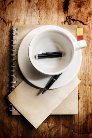 Empty cup of coffee with grunge notepad and pen on white tablecloth background,warm tone,still light photography. photo