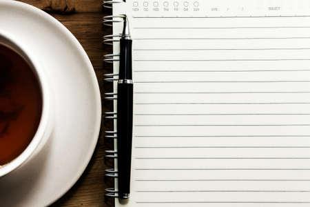 紅茶のカップ、スパイラル ノート、木製のテーブル バック グラウンド上のペン