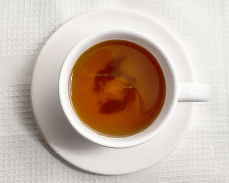 Top view cup of hot tea against white napkin on wooden background. photo