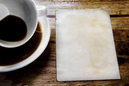 Cup of coffee with grunge notepad on wooden background  photo