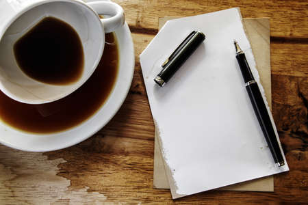 Cup of coffee with grunge notepad and pen on wooden background  photo