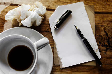 Cup of coffee with notepad, pen and crumpled paper on wooden background  photo