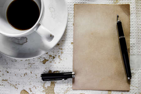 Cup of coffee with grunge notepad and pen on white tablecloth background  photo