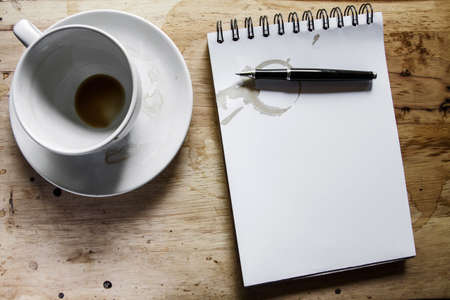 coffee stain: Coffee cup, spiral notebook and pen on the wooden table background Stock Photo