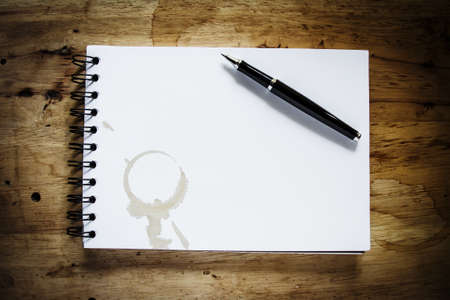 coffee stain on spiral book with pen on vintage wood table background. photo