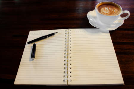 Coffee cup, spiral notebook and pen on the wooden table background photo