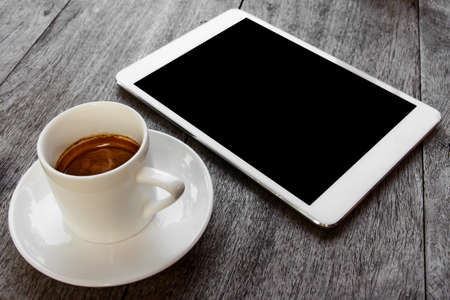 digital white tablet and coffee cup on wooden table  Standard-Bild