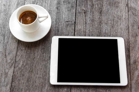 digital white tablet and coffee cup on wooden table  Stock Photo - 23151281