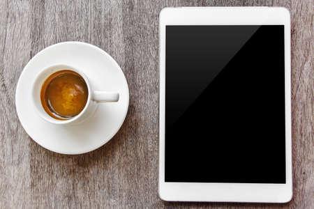 デジタル タブレットの白と木製のテーブルでコーヒー カップ