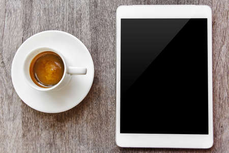 digital white tablet and coffee cup on wooden table  Stock Photo