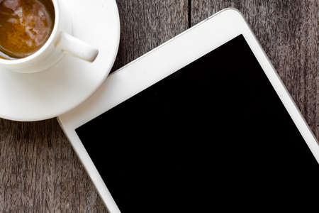 digital white tablet and coffee cup on wooden table Stock Photo - 23151292