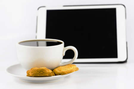 cup of coffee with cookie and tablet computer isolated on white background Stock Photo - 23324479