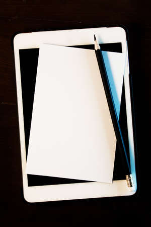 Close up blank white paper,classic pencil  with tablet computer on wooden background.Still life photography. photo