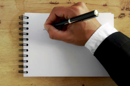 Abstract hand businessman writing on white paper. photo