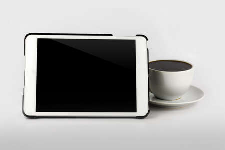 Tablet computer with white cup of coffee isolated on white background. photo
