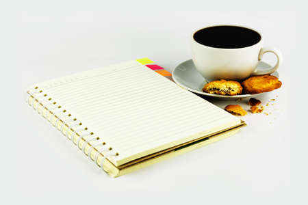cup of coffee with cookie and notebook isolated on white background photo