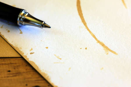 Close up pen with blank white paper on wooden background.Still life photography. photo