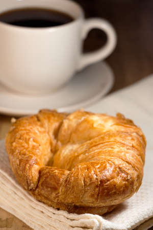 White cup of coffee and croissant on wooden table photo