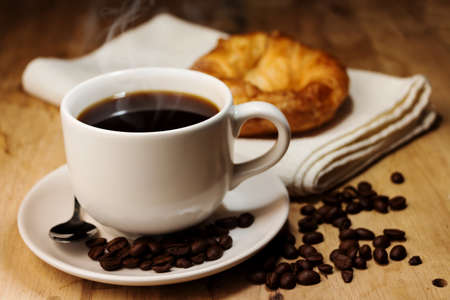 コーヒー、クロワッサン、木製のテーブルでコーヒー豆の白いカップ