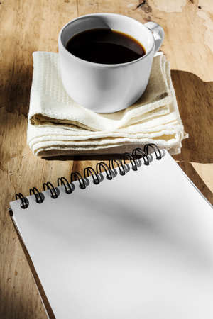 Sketchbook and instant coffee in white cup against wood background photo