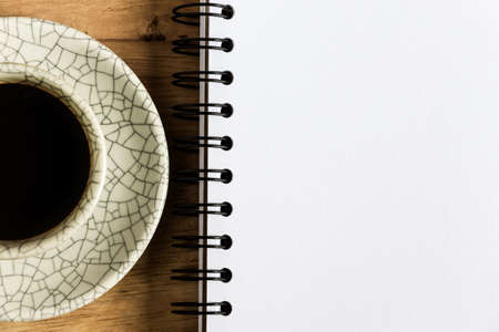 Sketchbook and instant coffeeagainst wood background photo