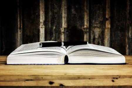 pen with open book on wood table against grunge background photo