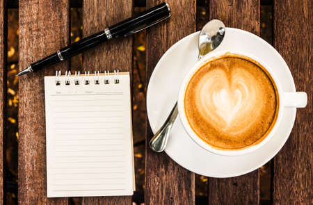 Open a blank white notebook, pen and cup of coffee on wood desk  photo