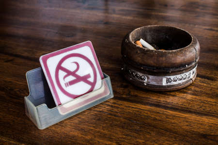 No smoking sign and vintage wood ashtray on table