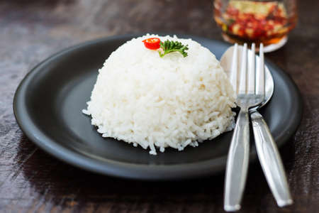 cooked rice: cooked rice with a spoon and fork on dish Stock Photo