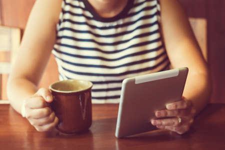 vintage woman: Asian woman using tablet computer in cafe drinking coffee. Focus on tablet. (Vintage process tone)