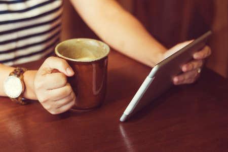 アジアの女性は、コーヒーを飲みながらカフェでタブレット コンピューターを使用して。タブレットに焦点を当てます。(ヴィンテージ プロセス ト