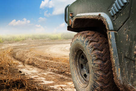 4wd: The wheels of car go round on dirt road.