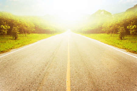Road in forest against mountain and sky background with light bursts.
