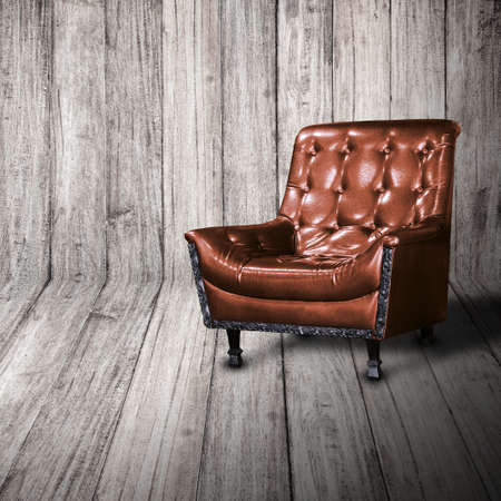 sofa: Leather Sofa against wood wall on perspective floor.