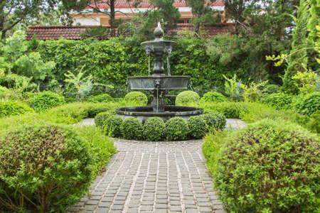 自然の背景。英国式庭園デザインの噴水。