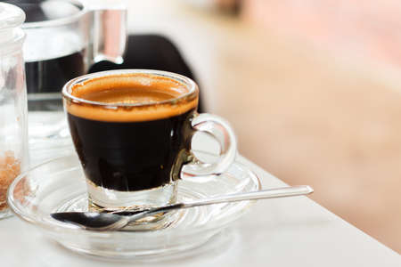 crema: Coffee cup. Hot espresso with golden crema on white table in cafe.