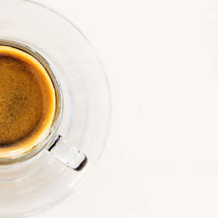 crema: Coffee cup. Hot espresso with golden crema on white table in cafe. Top view