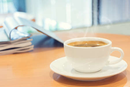 White cup of coffee with magazine on wood table in cafe. Selective focus.