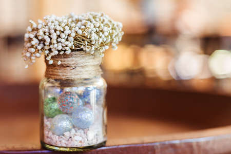 Interior room: Dried flowers in glass bottle on wood table decorations in cafe. Selective focus. Stock Photo