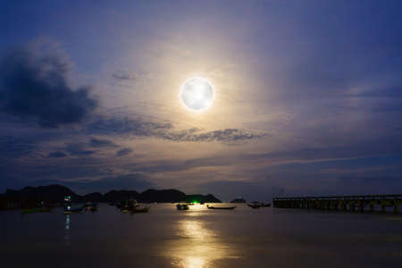 Moon rises over the fishing pier. Long exposure.  Stock Photo